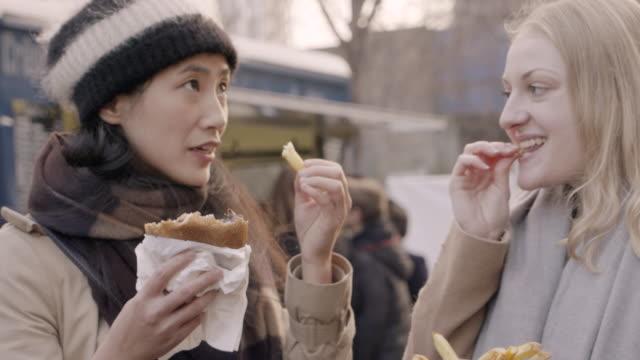 Women sharing street food at outdoor street market.