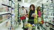 Women shopping with digital tablet in supermarket
