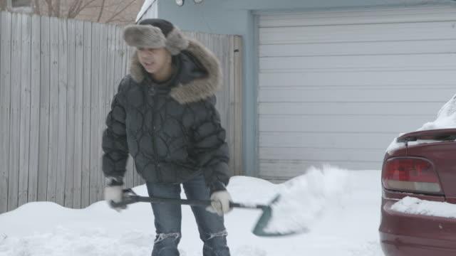 MS Women shoveling snow in driveway