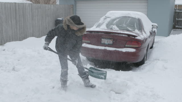 WS Women shoveling snow in driveway