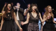 Women singing together on stage with band in background / Spanish Fork, Utah, United States,