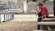 A women sits alone on a park bench. New York is behind
