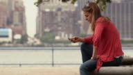 A women sits on a bench in a park and checks her phone.  New York city is behind