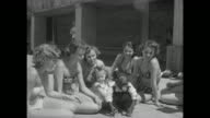 Women sitting in circle with little girl two women trying to hold chimpanzee who struggles to get away / chimp runs away / chimp sits in middle of...