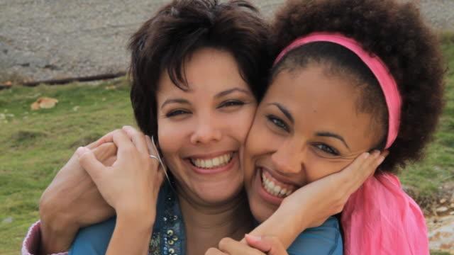 CU Women sitting on grass hugging each other / Havana, Cuba