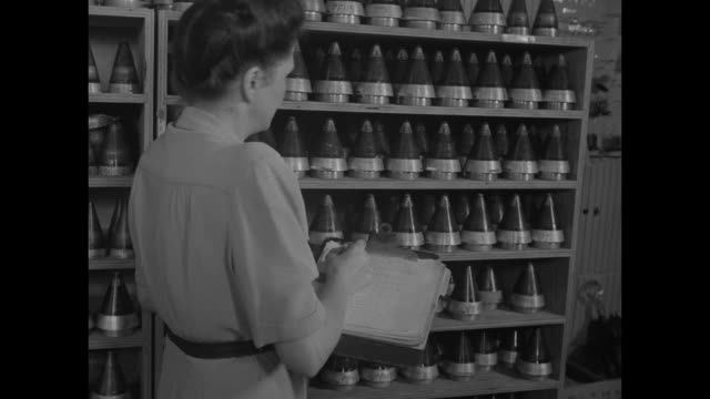 VS women solder use hammer and work with small vials of liquid with shell nose cones / VS woman with clipboard inventories shelves of cone shaped...