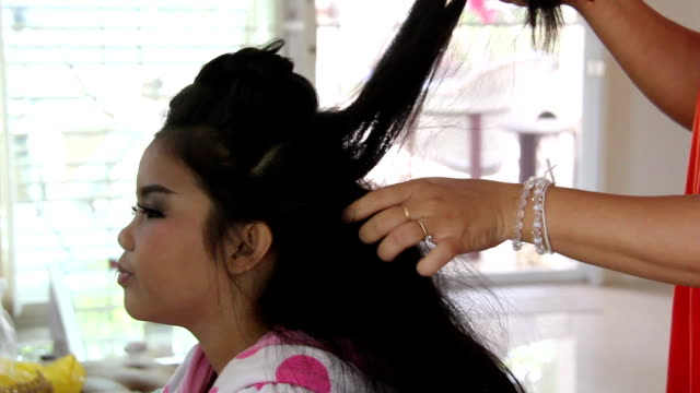 Women styling hair for Asia girl in house