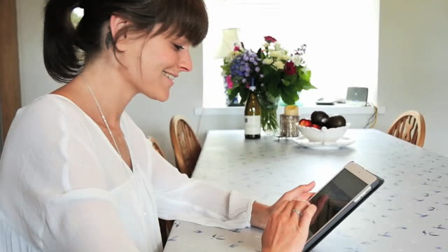 Women swipes tablet and laughs at kitchen table from side