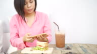 Women taking photo of breakfast with iced chocolate on wooden table with smartphone.