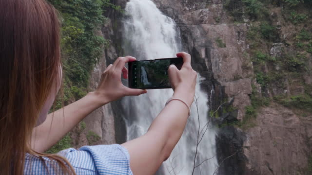 Women Taking Photo With Smart Phone At Waterfall In Khao Yai National Park