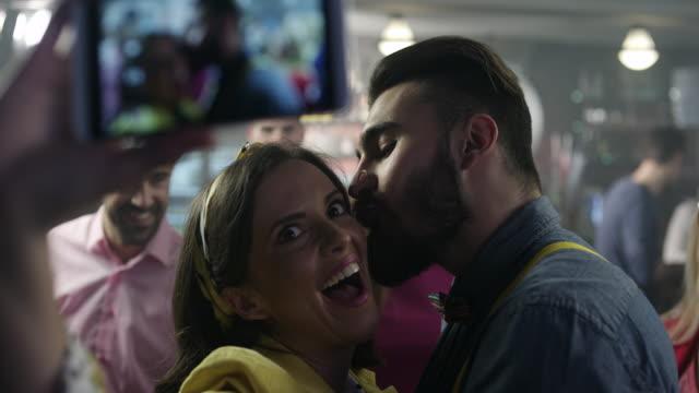 Women taking selfie while her boyfriend kisses her