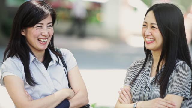 Women Talking on Busy Street