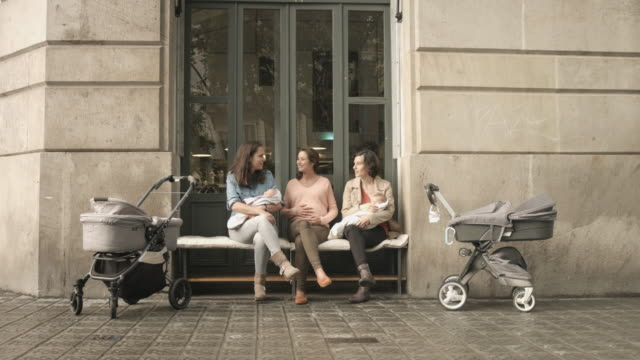 Women talking while carrying babies outdoors