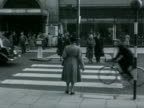 A women tentatively crosses Kensington High Street using one of the new zebra crossings 1951