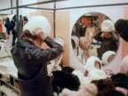 Women try on various hats in the millinery section of a department store