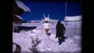 1969 women unloading car and carrying furniture up snowy path
