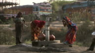 Women use a water pump beside a busy road.