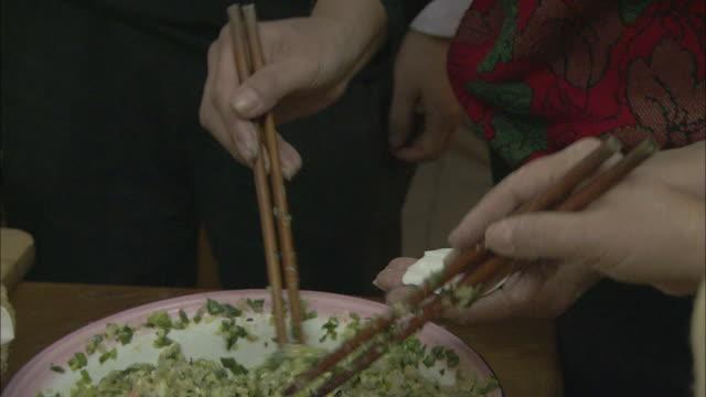 Women use chopsticks to fill dumplings.