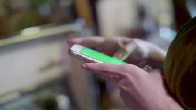 Women Using Green Screen On Mobile Phone At Home