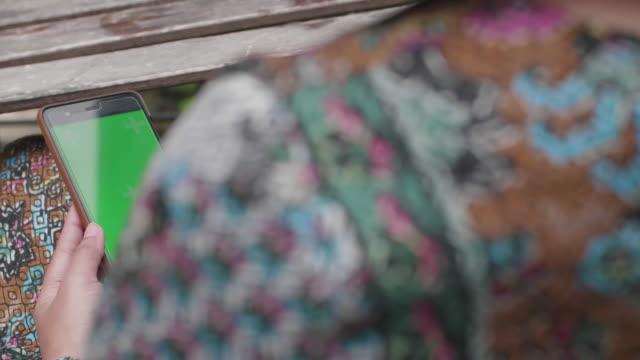 Women Using Green Screen On Mobile Phone