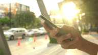Women using smart phone with sunset