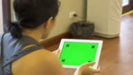 women using tablet phone with green screen
