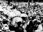 HA WS Women w/ shade umbrellas walking through crowd waving US flags VS Suffragettes on sidewalk selling newspapers one w/ chest banner 'Vote wo'...