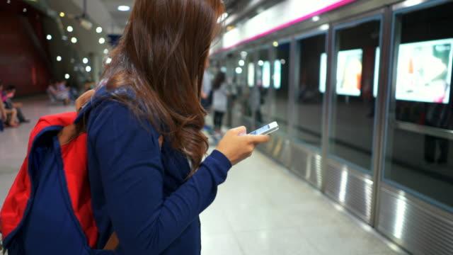 Frauen warten der Zug mit Smartphone und