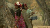 Women walk through a village. Available in HD