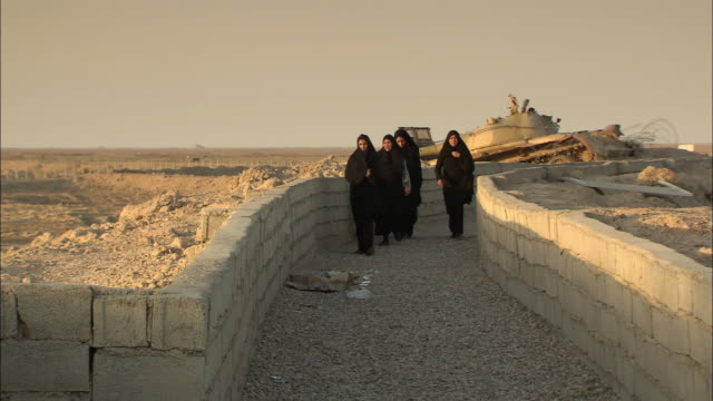 WS Women walking Near tank at Iran-Iraq border / Khorramshahr, Khuzestan Province, Iran