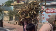 MS PAN Women walking through crowded street carrying bundles of sticks on heads, Districts of Delhi, India