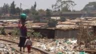 Women walking with child through garbage Kibera slum Nairobi Kenya Garbage Kibera slum Nairobi Kenya on February 13 2011 in Nairobi Kenya