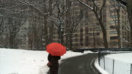 WS Women walking with red umbrella on path in Central Park during winter / New York City, New York, USA