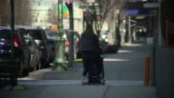 A women walks down the street with a stroller