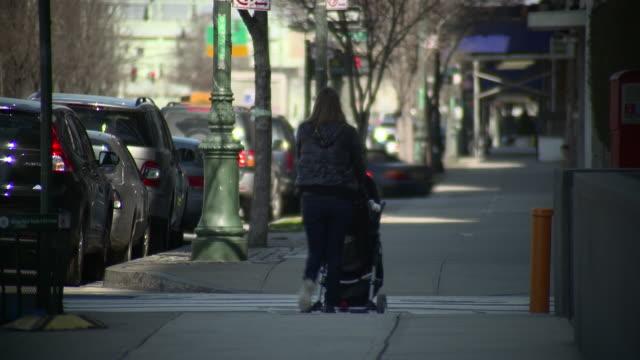 A women walks down the street with a stroller