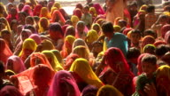 Women wearing colourful saris listen to public announcement seated Rajasthan Available in HD.