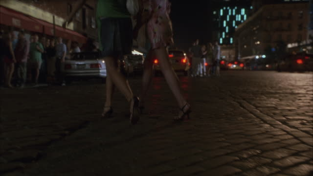 Women wearing high heels approaching a queue to a nightclub.