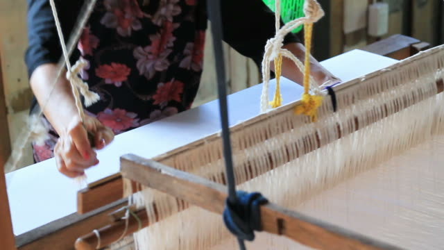 Women weaving cotton on a loom in Thailand