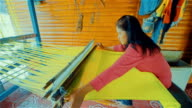 Women weaving the silk threads into fabric on a loom at home in countryside of Thailand