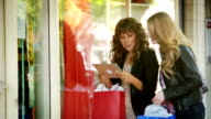 Women window shopping with tablet