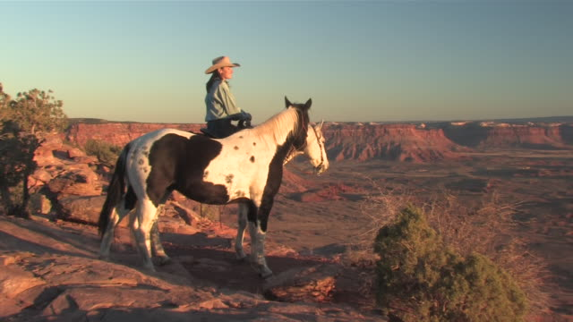 MS ZO Women with Horses over looking spectaculair Red Rock Canyons, Majestic Western Landscapes at sunset / Telluride, Colorado, United States