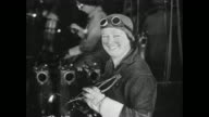 women working in Ford defense factory / woman worker removes goggles smiles for camera man shakes woman's hand and gives her a liberty bond...