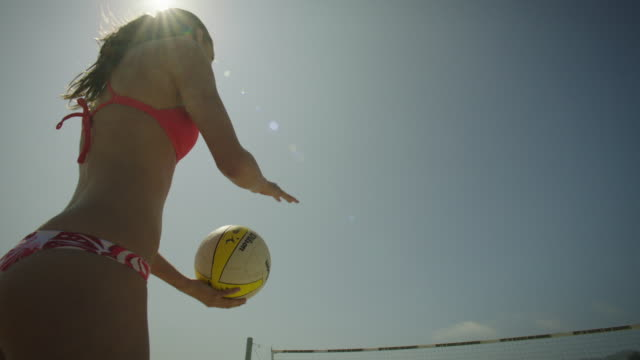 Women's Beach Volleyball Player serves the ball in slow motion, from a low wide-angle looking up at the blue sky and sun