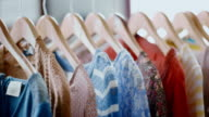 Women's shirts with various patterns and designs hang from rack in modern clothing store