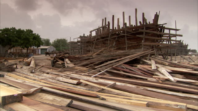 Wood beams and planks surround a wooden ship at a construction yard. Available in HD.