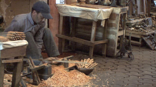 MS Wood carver in Souk working with hand and foot, Marrakech, Morocco