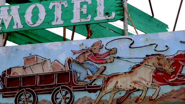 Wood neon sign w/ depiction of stagecoach driver galloping horses blue wooden sign above reading Motel