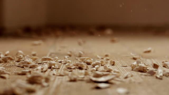 Wood shavings falling on the floor.