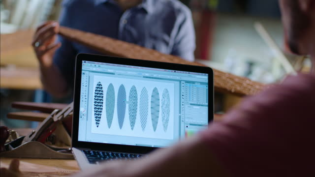 Wood shop worker on laptop computer studies intricate skateboard designs