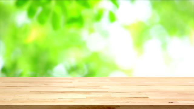 wood table top on blur moving green leaf background stock